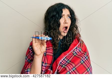 Young brunette woman with curly hair wrapped in a blanket holding thermometer angry and mad screaming frustrated and furious, shouting with anger. rage and aggressive concept.