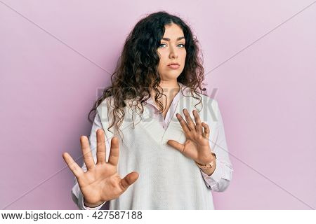 Young brunette woman with curly hair wearing casual clothes moving away hands palms showing refusal and denial with afraid and disgusting expression. stop and forbidden.