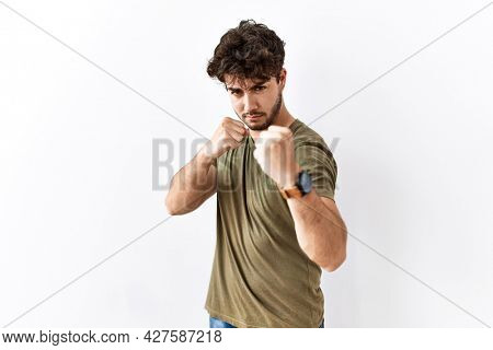 Hispanic man standing over isolated white background ready to fight with fist defense gesture, angry and upset face, afraid of problem