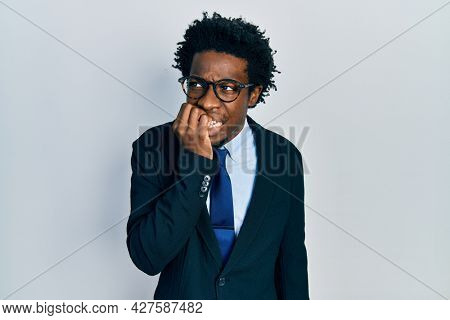 Young african american man wearing business suit looking stressed and nervous with hands on mouth biting nails. anxiety problem.