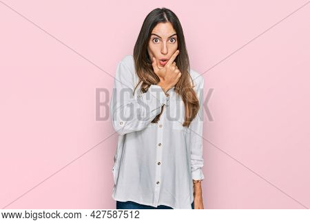 Young beautiful woman wearing casual clothes looking fascinated with disbelief, surprise and amazed expression with hands on chin