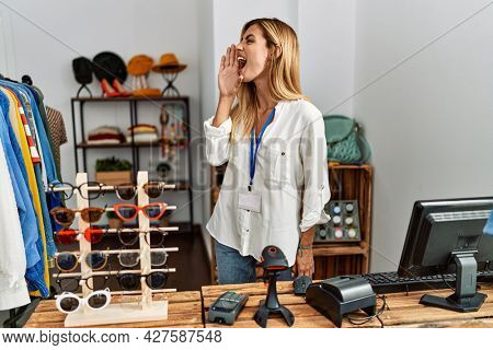 Blonde beautiful young woman working as manager at retail boutique shouting and screaming loud to side with hand on mouth. communication concept.