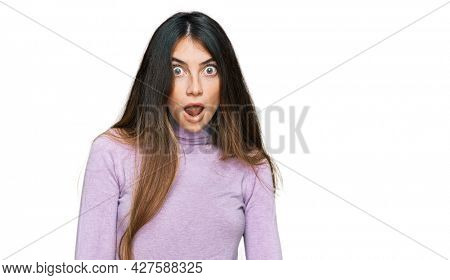Young beautiful teen girl wearing turtleneck sweater afraid and shocked with surprise and amazed expression, fear and excited face.