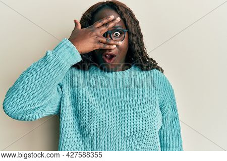 African young woman wearing casual clothes and glasses peeking in shock covering face and eyes with hand, looking through fingers afraid
