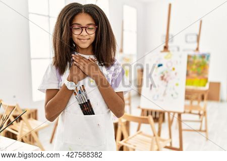 Young african american girl painting at art studio smiling with hands on chest with closed eyes and grateful gesture on face. health concept.