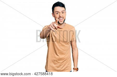 Hispanic man with beard wearing casual t shirt pointing displeased and frustrated to the camera, angry and furious with you