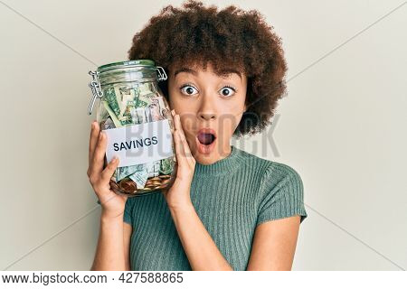 Young hispanic girl holding jar with savings afraid and shocked with surprise and amazed expression, fear and excited face.