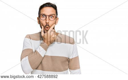 Handsome man with beard wearing casual clothes and glasses looking fascinated with disbelief, surprise and amazed expression with hands on chin