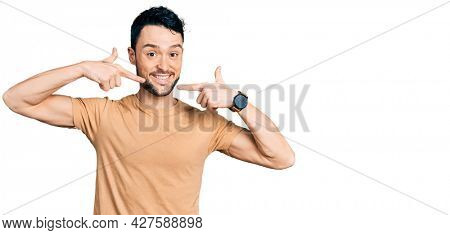 Hispanic man with beard wearing casual t shirt smiling cheerful showing and pointing with fingers teeth and mouth. dental health concept.