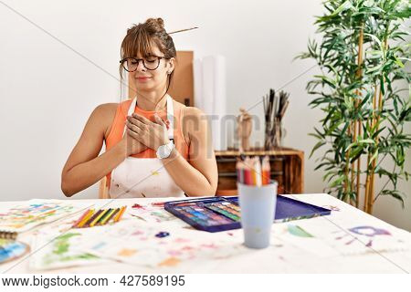 Hispanic woman at art studio smiling with hands on chest with closed eyes and grateful gesture on face. health concept.