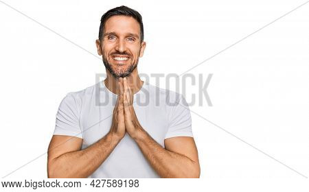 Handsome man with beard wearing casual white t shirt praying with hands together asking for forgiveness smiling confident.