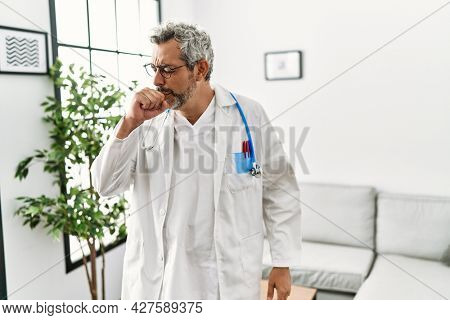 Middle age hispanic man wearing doctor uniform and stethoscope at waiting room feeling unwell and coughing as symptom for cold or bronchitis. health care concept.