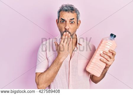 Handsome middle age man with grey hair holding detergent bottle covering mouth with hand, shocked and afraid for mistake. surprised expression