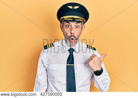 Handsome middle age man with grey hair wearing airplane pilot uniform surprised pointing with hand finger to the side, open mouth amazed expression.