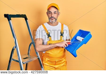 Handsome middle age man with grey hair holding roller painter relaxed with serious expression on face. simple and natural looking at the camera.