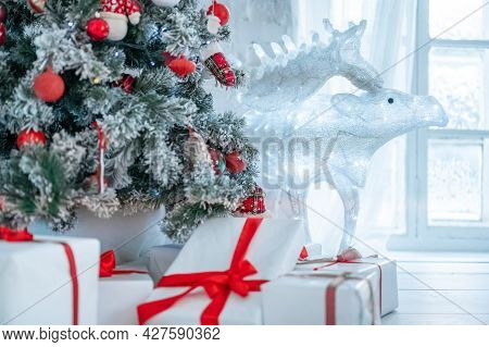 Christmas Tree And Gift Boxes In Interior With Deer. Christmas Card. Christmas Tree Decorated With T
