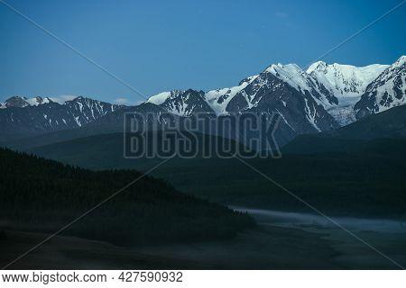Atmospheric Misty Mountain Landscape With Great Snow Mountain Top Under Twilight Sky. Alpine Misty S