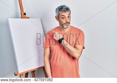 Handsome middle age man with grey hair standing by painter easel stand pointing with hand finger to the side showing advertisement, serious and calm face