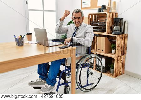 Middle age hispanic man working at the office sitting on wheelchair angry and mad raising fist frustrated and furious while shouting with anger. rage and aggressive concept.