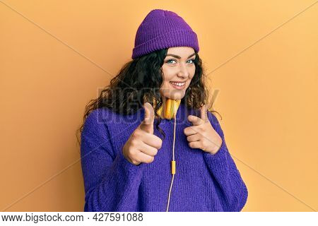 Young brunette woman with curly hair listening to music using headphones pointing fingers to camera with happy and funny face. good energy and vibes.