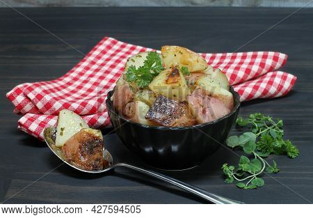A Black Bowl Of Grill Roasted Red Potatoes With Oregano And Parsley To The Side.  A Tablespoon Of Po