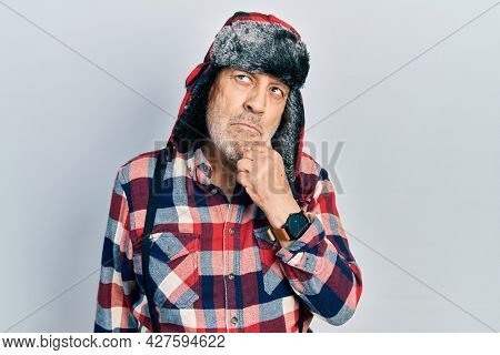 Handsome mature man wearing winter hat with ear flaps serious face thinking about question with hand on chin, thoughtful about confusing idea