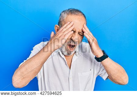 Handsome senior man with beard wearing casual white shirt with hand on head for pain in head because stress. suffering migraine.