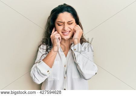 Beautiful middle eastern woman wearing casual clothes covering ears with fingers with annoyed expression for the noise of loud music. deaf concept.