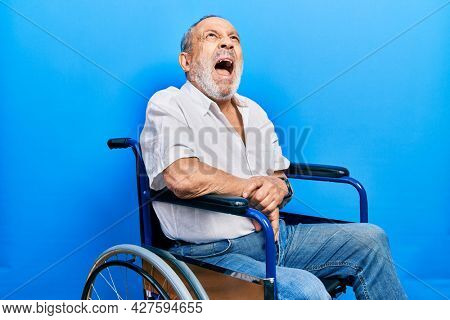 Handsome senior man with beard sitting on wheelchair angry and mad screaming frustrated and furious, shouting with anger. rage and aggressive concept.