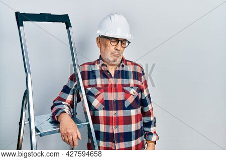 Handsome mature handyman close to construction stairs wearing hardhat depressed and worry for distress, crying angry and afraid. sad expression.