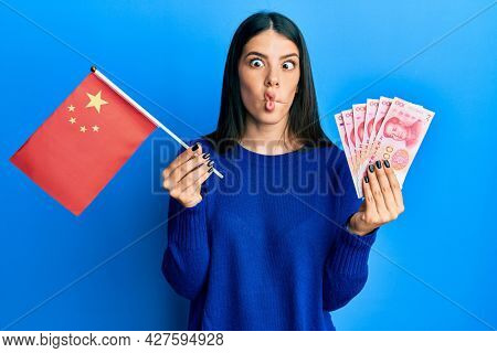 Young hispanic woman holding china flag and yuan banknotes making fish face with mouth and squinting eyes, crazy and comical.