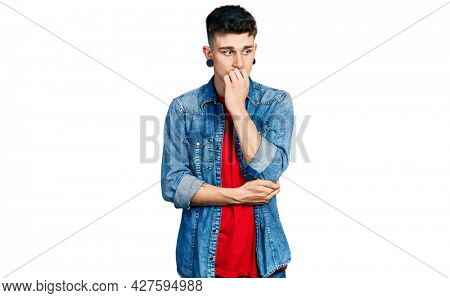 Young caucasian boy with ears dilation wearing casual denim jacket looking stressed and nervous with hands on mouth biting nails. anxiety problem.