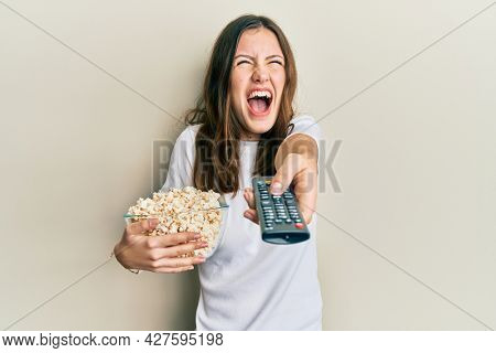 Young brunette woman eating popcorn using tv control angry and mad screaming frustrated and furious, shouting with anger looking up.