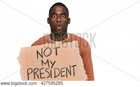Young african american man holding not my president protest banner scared and amazed with open mouth for surprise, disbelief face