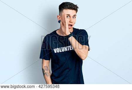 Young caucasian boy with ears dilation wearing volunteer t shirt hand on mouth telling secret rumor, whispering malicious talk conversation