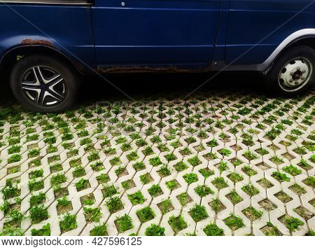 Blue Car On Eco Friendly Parking Lot Made Of Concrete With Cells For Grass Germination, Copy Space.