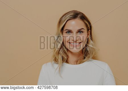 Enjoying Life. Studio Shot Of Young Pretty Female With Wavy Hair In White Tshirt Looking With Satisf