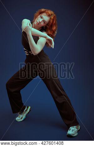 Modern dance style. Professional modern style dancer girl dancing at studio on a dark blue background