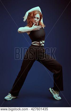Professional modern style dancer girl dancing at studio on a dark blue background. Modern dance style.
