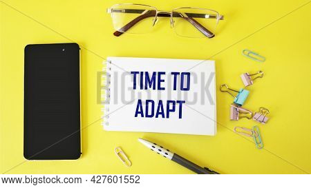 Time To Adapt Text Written On Notepad And Yellow Background With Mobile Phone And Pen