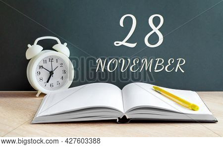 November 28. 28-th Day Of The Month, Calendar Date.a White Alarm Clock, An Open Notebook With Blank