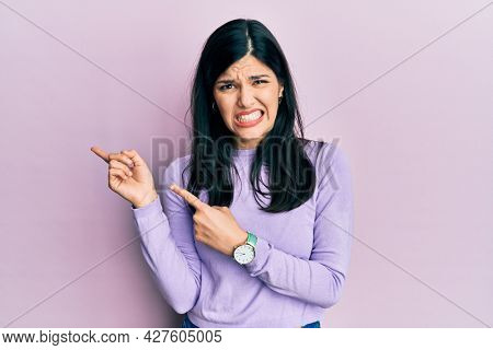 Young hispanic woman wearing casual clothes pointing aside worried and nervous with both hands, concerned and surprised expression