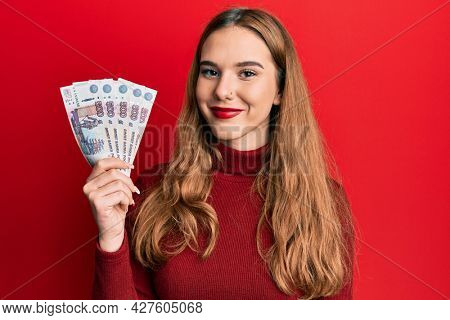 Young blonde woman holding russian 500 ruble banknotes looking positive and happy standing and smiling with a confident smile showing teeth