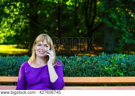 Defocus Caucasian Blond Smiling Woman Talking, Speaking On The Phone Outside, Outdoor. 40s Years Old