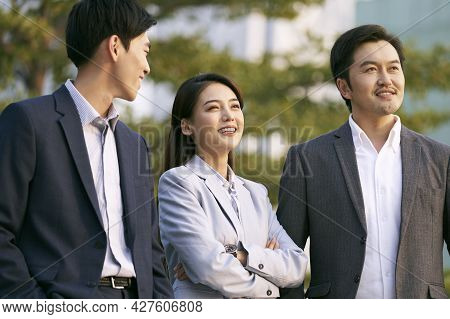 Team Of Three Asian Businesspeople Chatting Talking Conversing Outdoors