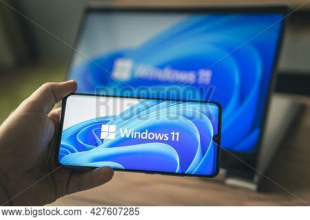 June 23, 2021. Barnaul, Russia. Man With A Laptop And A Smartphone, Windows 11 New Microsoft Operati