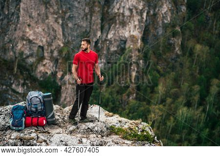 A Traveler With A Backpack In The Mountains. A Man With A Backpack. The Concept Of A Hiking Lifestyl