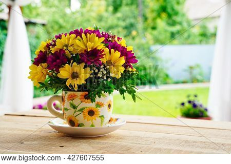 Composition Of Flowers In A Tea Mug On A Wooden Table In The Morning In Summer Or Spring. Postcard G