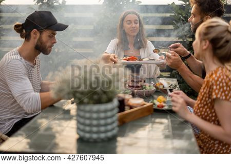 Small Group Of A Young Friends Have A Lunch Outdoors, Eating Grilled Vegetables And Fish And Having