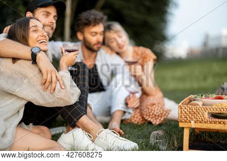 Young Friends Sit Together And Hug, Talk And Drink Wine In A Close And Friendly Atmosphere On A Picn